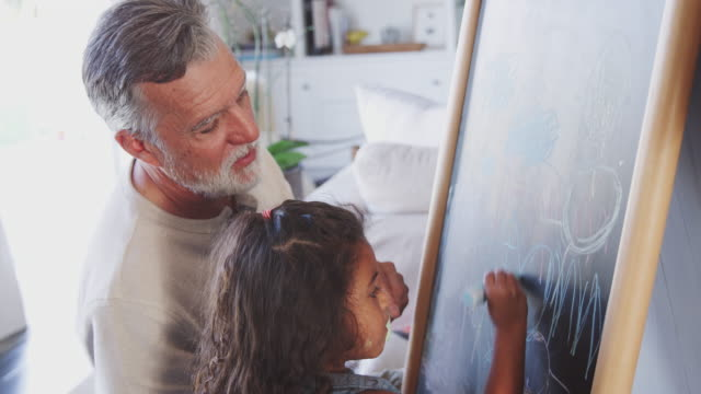 Senior man drawing on a blackboard with his young granddaughter at home Senior man drawing on a blackboard with his young granddaughter at home granddaughter stock videos & royalty-free footage