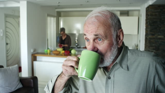 Senior man drinking coffee at home video