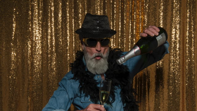 A senior man drinking wine and wearing fun props while taking photos in the photo booth