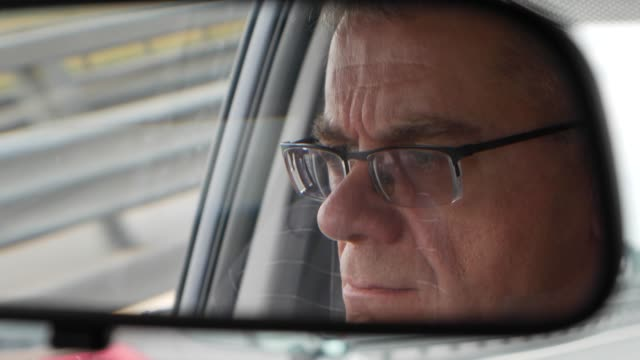 Senior man drives a car at the country road. Reflection of face in the rearview mirror of the auto. Closeup. 4k Senior man drives a car at the country road. Reflection of face in the rearview mirror of the auto rear view mirror stock videos & royalty-free footage