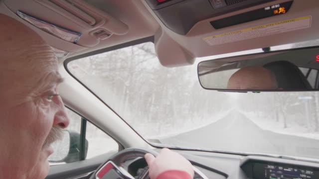 Senior man driving a car under the snow