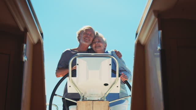 Senior man embracing woman while steering yacht
