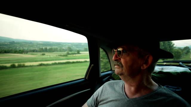 vídeos de stock e filmes b-roll de senior man enjoying the ride - old men window