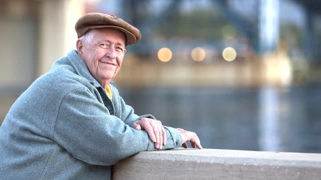 vidéos et rushes de senior homme appréciant le front de mer, se tourne vers le sourire à la caméra - grand père