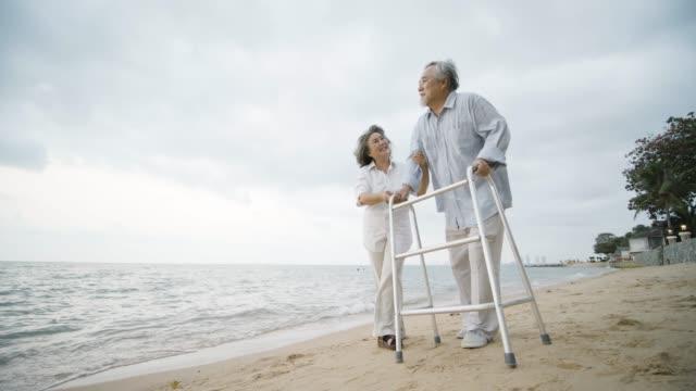ウォーカーと彼の妻と年配の男性の運動は、スローモーションでビーチを歩いている彼を支援します。医療、医療人と退職のコンセプト。 ビデオ