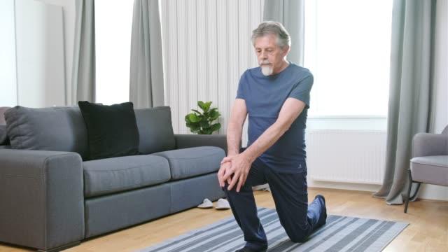거실에서 운동 하는 수석 남자 - 레저 활동 스톡 비디오 및 b-롤 화면