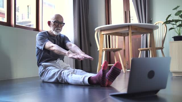 居間で運動する先輩男性 - disruptagingcollection点の映像素材/bロール
