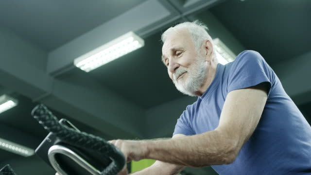 Senior man exercising on stationary bike Senior man exercising on stationary bike in gym. exercise bike stock videos & royalty-free footage