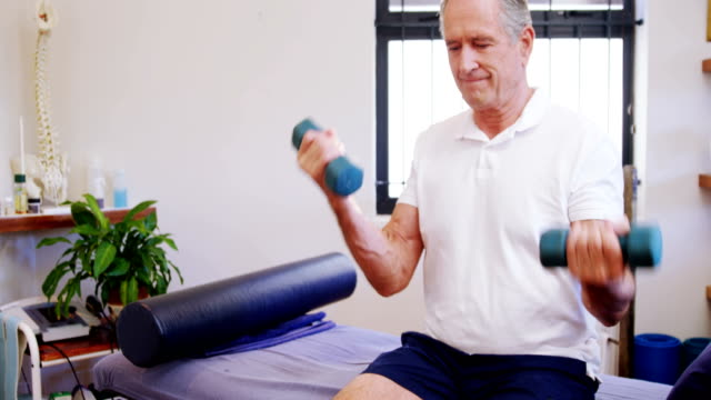 Senior man exercising with dumbbells 4k video