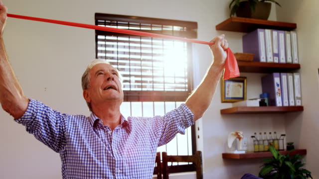 Senior man exercising with resistance band 4k video