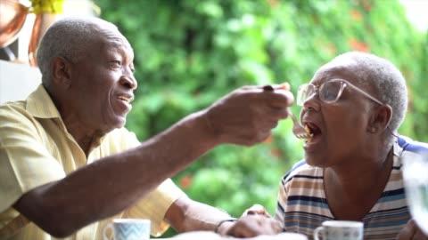 vidéos et rushes de homme aîné alimentant sa femme pendant le thé de l'après-midi - manger