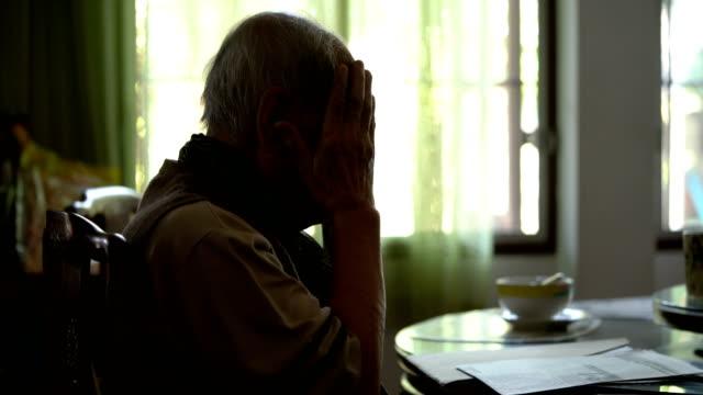 Senior man feeling headache while reading a newspaper