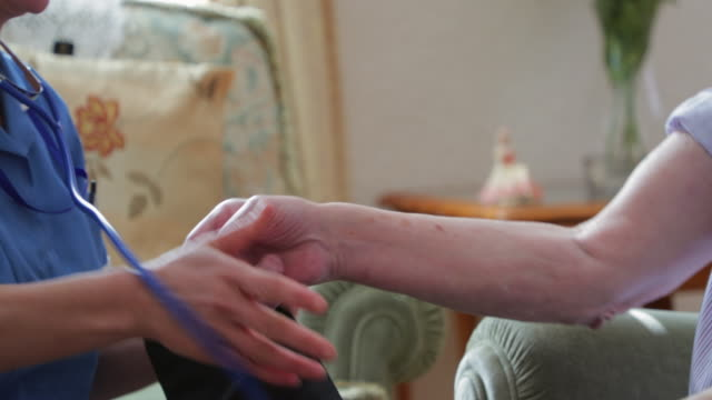 Senior Man Finishing Up his Check up With the Nurse Nurse removing the blood pressure machine from the senior man after having his home checkup nhs stock videos & royalty-free footage