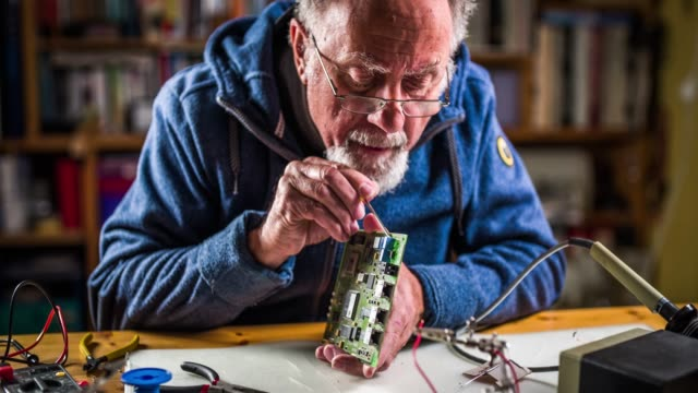 Senior man fixing  electronic components Senior man repairing a circuit board in his workshop. He is removing a defect component. hobbies stock videos & royalty-free footage