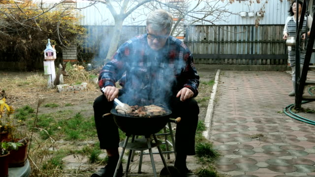 Senior man fries meat on barbecue in backyard of house. Woman carries pot across yard. Senior man fries meat on barbecue in backyard of house. Woman carries pot across yard. They are talking. Concept of real life of married couples in age. Medium plan. Outdoors. pantry stock videos & royalty-free footage
