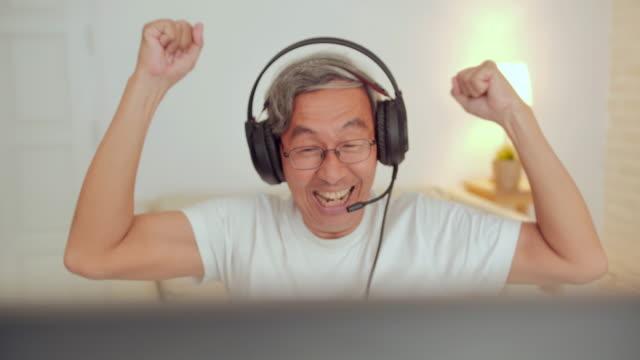 Senior man gamer playing and winning in online video game.Senior men gamer playing video game wearing headphone.eSport Cyber Games Internet.Senior Technology,Lifestyle,Vision,Innovation,Retirement concept. video