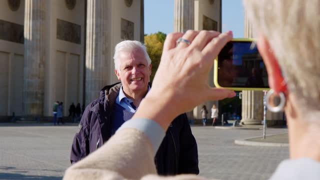 Senior man getting his picture taken by his wife at Brandenburg gate