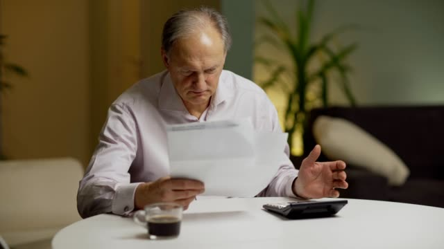 Senior man getting stressed and putting head in hands after looking at paper bills and calculating expenses sitting at table at home
