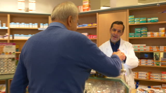 vidéos et rushes de senior homme donnant sur ordonnance à votre pharmacien - pharmacie