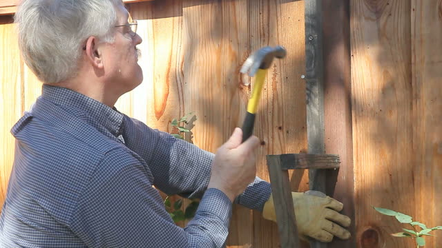 senior man hammering on fence - nail work tool stock videos & royalty-free footage