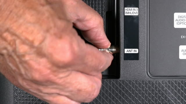 Senior man hand cutting the cord on his cable TV package Close up of senior caucasian man hand removing the aerial connection to his TV to illustrate cutting the cable TV cord cable tv stock videos & royalty-free footage