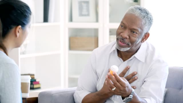 Senior man has serious conversation with doctor about medication Serious senior African American man has a serious conversation with his doctor about his medication. He gestures as he asks the doctor questions about his medication. He has an uncertain expression on his face as he talks with the doctor. The doctor listens attentively to the man and then answers his questions. prescription stock videos & royalty-free footage