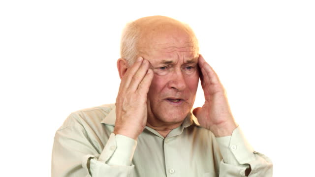 Senior man having a headache rubbing his temples video