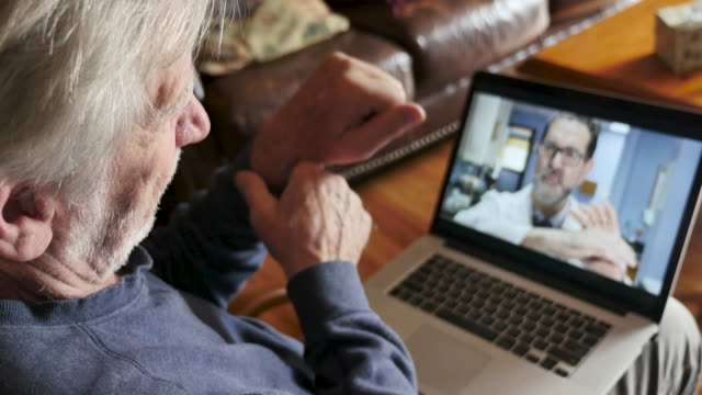 senior man having a virtual exam during a telemedicine appointment - fisioterapia video stock e b–roll