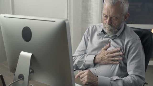 vídeos de stock e filmes b-roll de senior man having an heart attack at home - enfarte