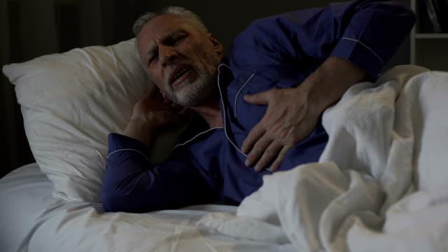 Senior man having heart attack, suffering sharp chest pain while sleeping video