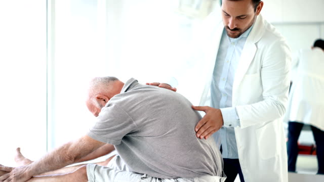 Senior man having his back examined by a doctor. 4k