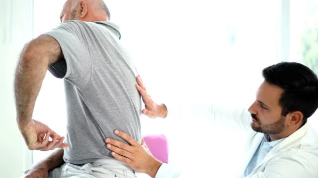 vídeos y material grabado en eventos de stock de senior hombre tener su espalda examinada por un médico. 4k - columna vertebral humana