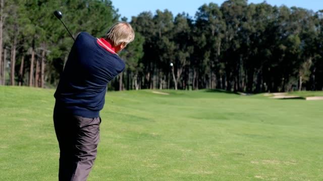Senior man hits a golf shot towards the putting green