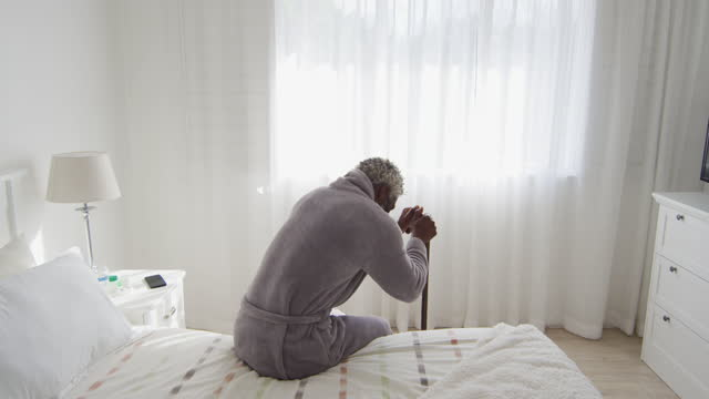 Senior man holding his walking stick while sitting on bed at home