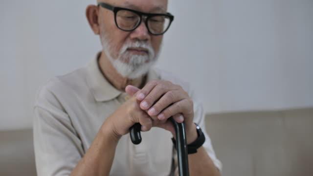 Senior man holding walking cane and looking at camera