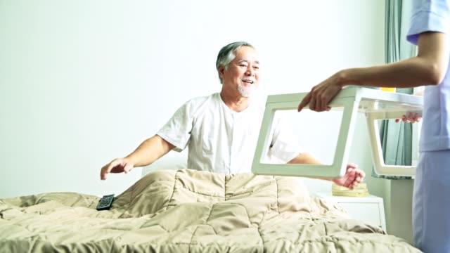 ベッドで年配の男性は、美人看護婦さんが朝食を提供します。若い魅力的なアジア女性世話人と白ひげとの古いのアジア系男性。高齢者ホーム サービス コンセプトです。 ビデオ