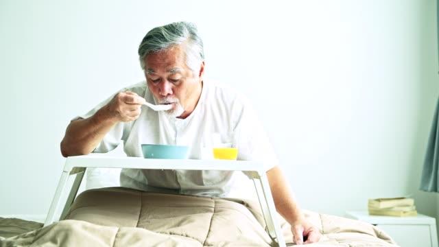 ベッドの朝食を楽しむ年配の男性。お粥とオレンジ ジュースを食べる白いひげと古いのアジア系男性。高齢者ホーム サービス コンセプトです。 ビデオ