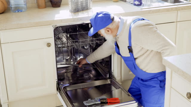 Senior man in blue overalls clean sink of the dishwasher Mature specialist repairs dishwasher at the kitchen. Old man wearing protective coveralls works as hired worker in someone's home. Prores codec. appliance stock videos & royalty-free footage