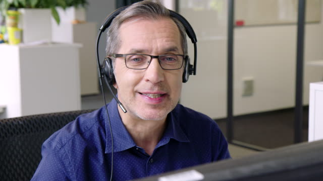Senior man in customer service position talking on the headset Close-up of mature businessman with headset working on computer. Senior man in customer service position talking on the headset. hands free device stock videos & royalty-free footage
