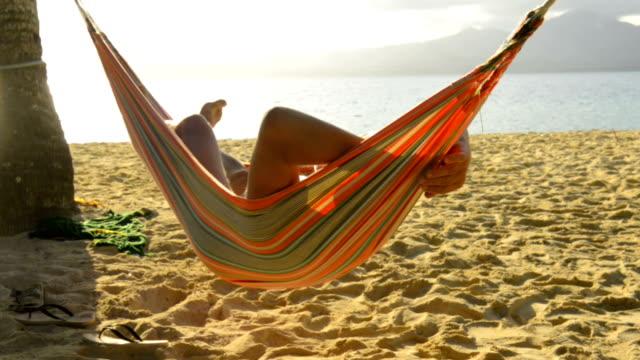 senior man in hammock on the beach - загар стоковые видео и кадры b-roll