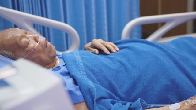 stockvideo's en b-roll-footage met hogere mens in het ziekenhuisbed dat zijn gezicht raakt - ventilator bed