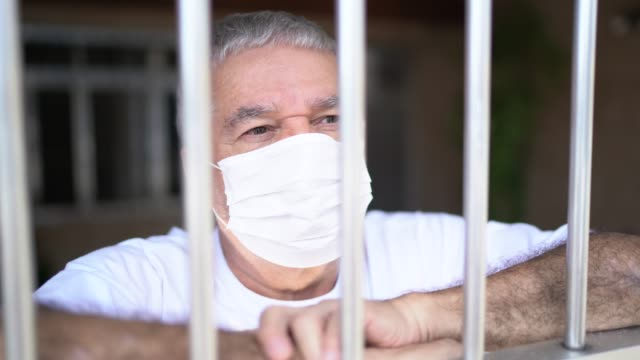 Senior man in isolation at home for virus outbreak looking through window