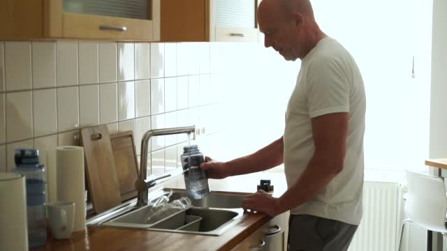 senior man in kitchen filling sport water bottle - acqua potabile video stock e b–roll