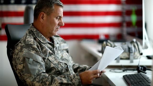 Senior man in military uniform doing paper work