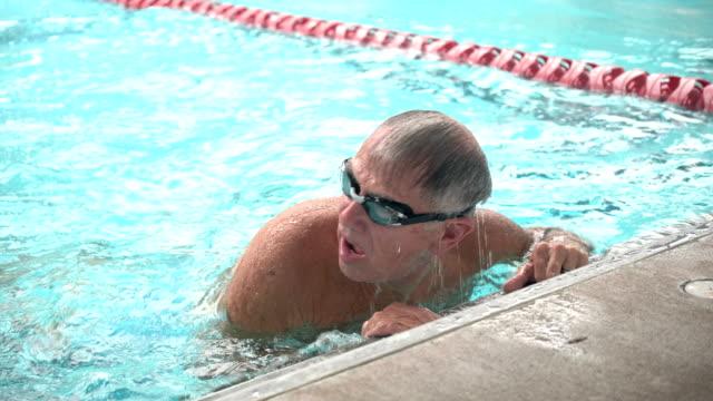 vídeos de stock e filmes b-roll de senior man in pool swimming laps - nadar