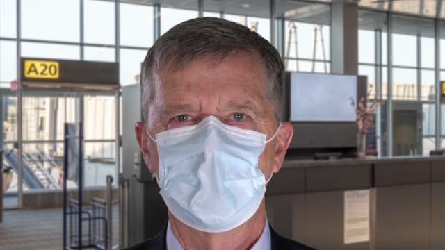 Senior man in portrait wearing face mask against Covid-19 and breathing deeply making the mask move in and out against airport background - video
