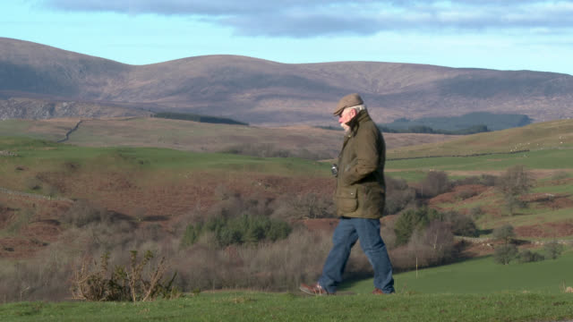 Senior man in rural setting entering frame camera right and using binoculars 4k footage shot at 50fps and interpreted at 25fps to give slower motion galloway scotland stock videos & royalty-free footage