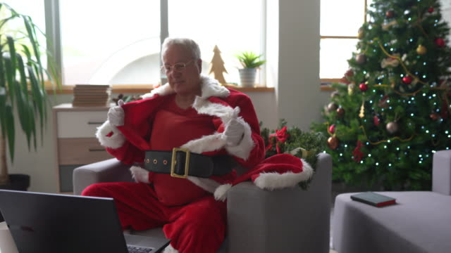 Senior man in Santa uniform finished his work from home during coronavirus pandemic