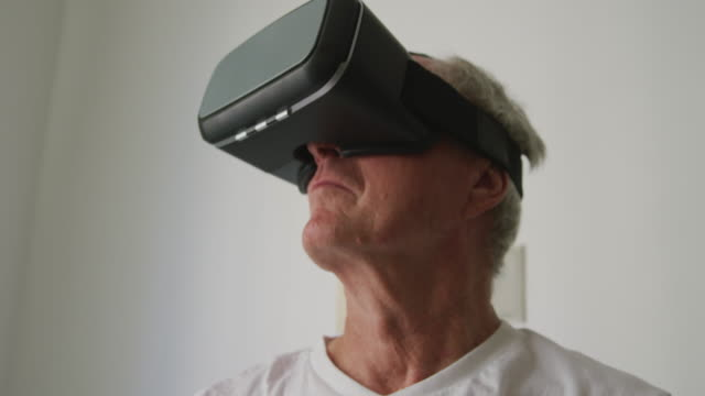 senior man in social distancing using vr headset - hand on glass covid video stock e b–roll