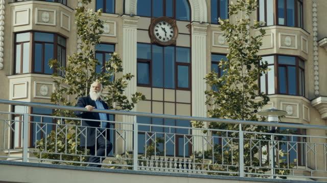 Senior man in suit enjoys city background video